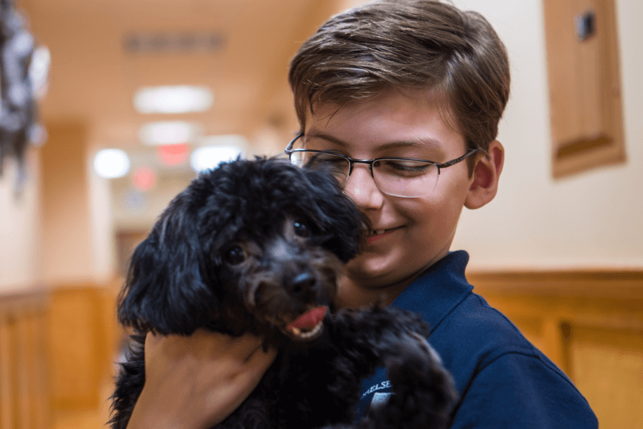 child holding black dog in hallway