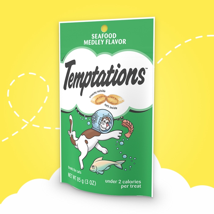green bag of temptations seafood medley flavored treats on yellow background